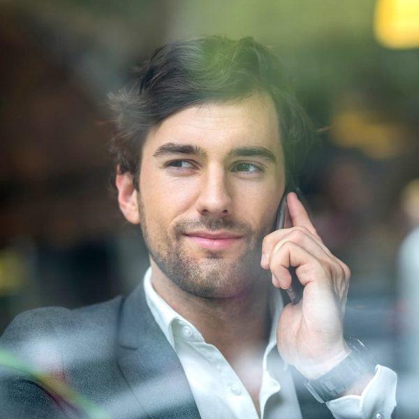 Sales professional voert telefoongesprek en kijkt uit raam