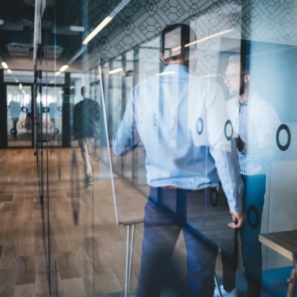 Twee commerciele mannen overleggen op kantoor